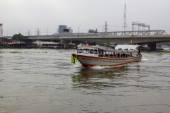 A Chao Phraya Express Boat approaches a pier on the Chao Phraya river